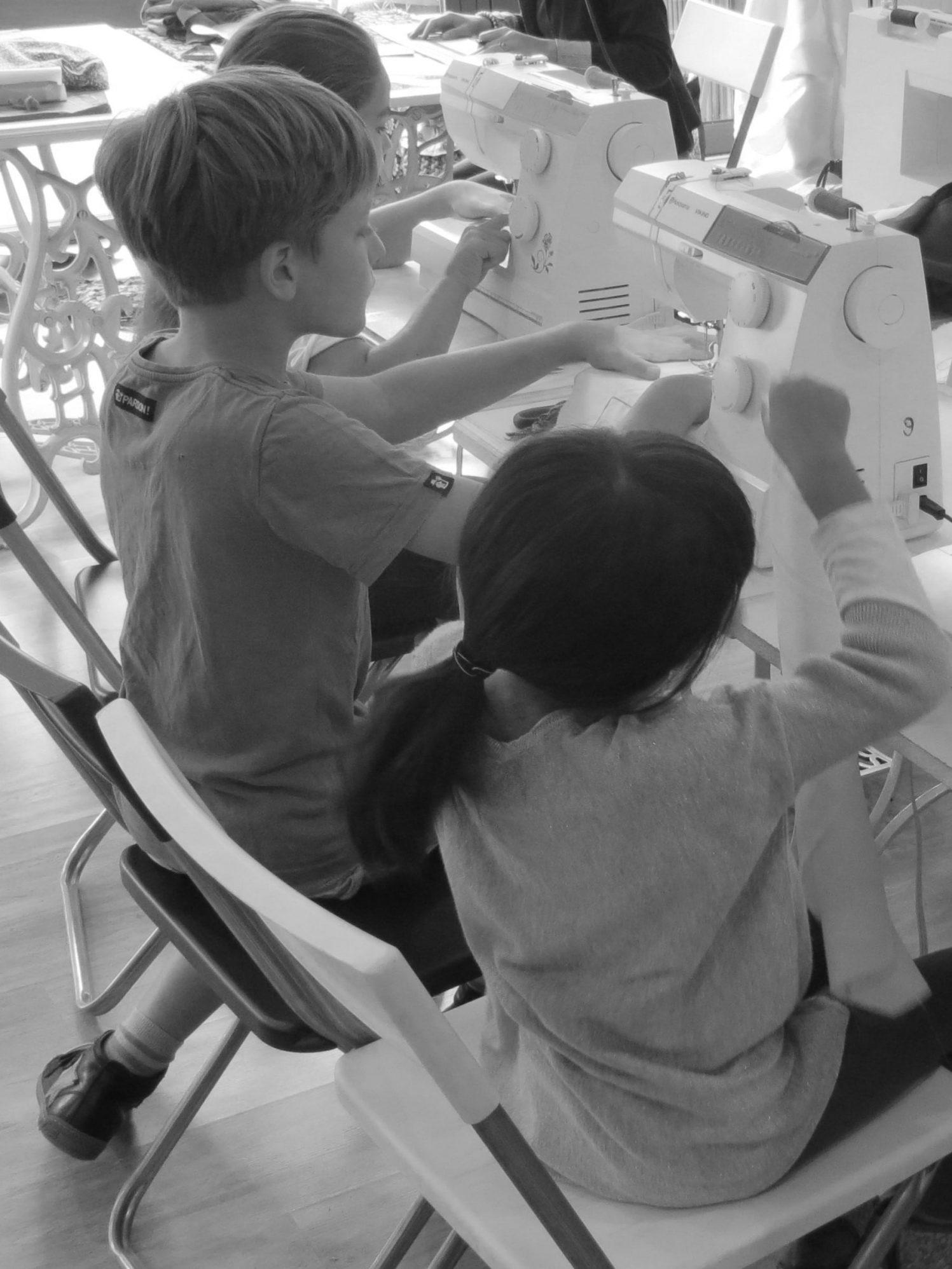 Les enfants devant les machines à coudre