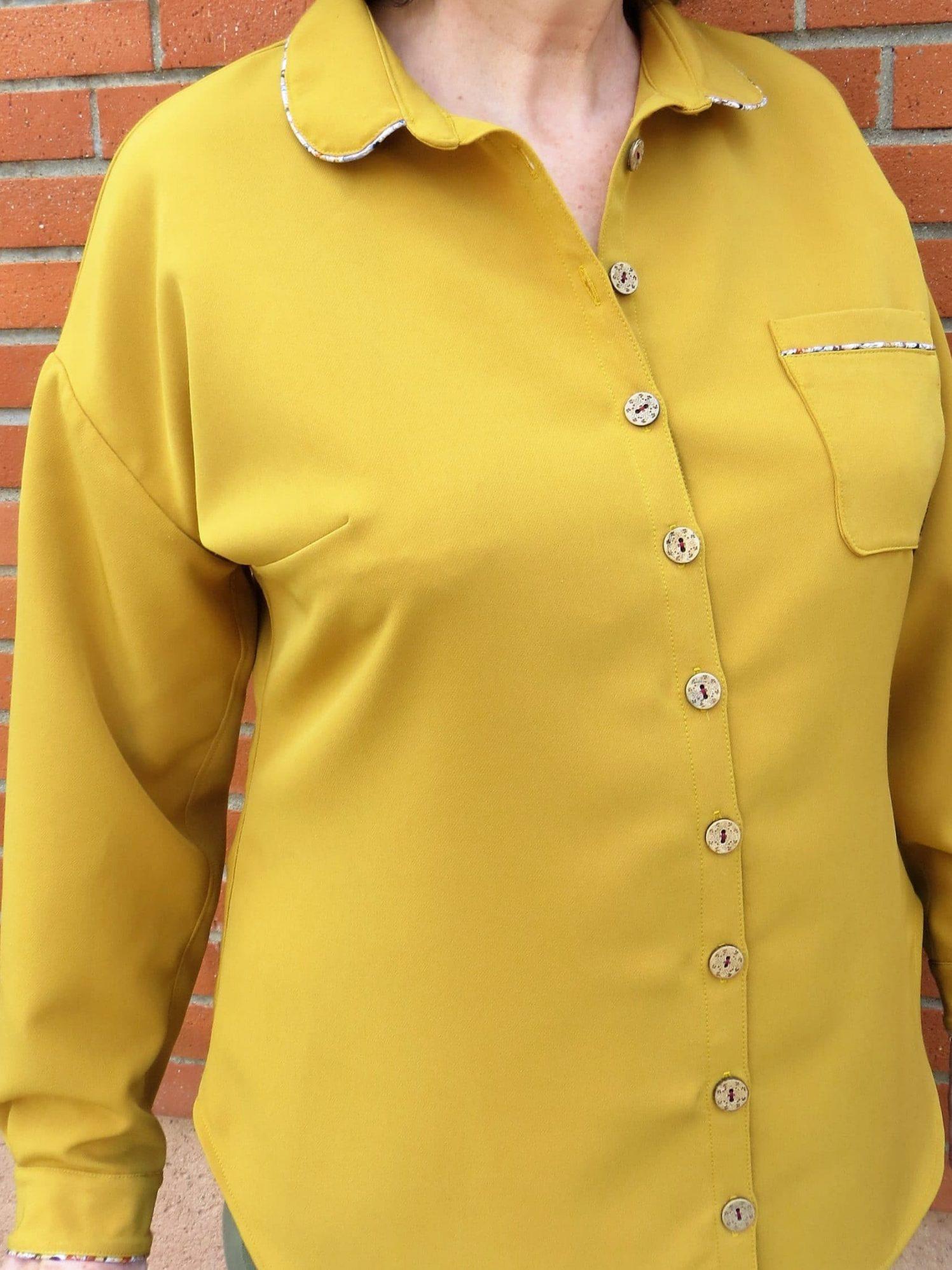 Une chemise manches longue, sa patte de boutonnage, détail de passepoil