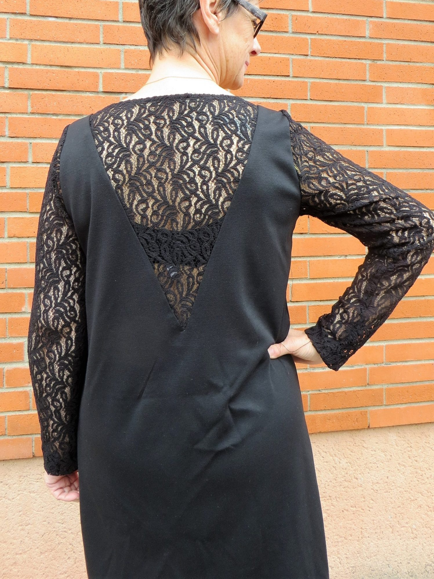 Une robe noir, manches en dentelle